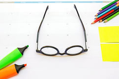 Business concept with vintage glasses, color pen, pencils and no. Te stick on calendar background Royalty Free Stock Photography