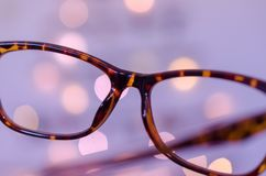 Business concept vision. Eyeglasses against bokeh Christmas lights background. Vision or business concept Royalty Free Stock Image