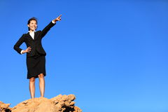 Business concept - woman pointing at future. Business concept - businesswoman pointing at future ahead standing on mountain top wearing suit stock photography