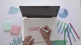 Business concept. Woman write LEADERSHIP on a piece of paper located on laptop.