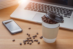 Business concept, work place with paper cup of roasted aroma cof. Fee beans, smart phone, laptop,  book and sunlight from background Royalty Free Stock Photo