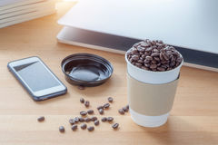 Business concept, work place with paper cup of roasted aroma cof. Fee beans, smart phone, laptop,  book and sunlight from background Stock Photography