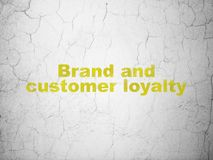 Business concept: Brand and Customer loyalty on wall background. Business concept: Yellow Brand and Customer loyalty on textured concrete wall background royalty free stock image