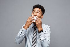 Business Concept - Young angry African American businessman while eating balled report paper. Unsuccessful Project. Stock Image
