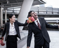 Business concept : Young Asian business woman in suit uniform wearing boxing gloves and punching business man`s face. Business concept : Young Asian business Stock Photos