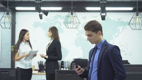 Business people working in office. Business concept. Young businessman in formal attire looks smartphone on background of two young female employees discussing stock video