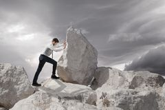 Business concept, Young businessman pushing large stone uphill with copy space Royalty Free Stock Photos