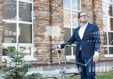 Business concept. Young man rolling his bicycle Stock Photos