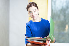 Business Concepts. Smiling Positive Caucasian Brunette Female With Folders Stock Photography