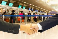 Business Conceptual Hand Shake With Passengers Check-in Line At The Airport. Royalty Free Stock Photos