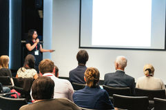 Business conference. People sitting rear and woman speaking at the screen royalty free stock photo