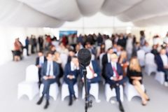 Business conference. Corporate presentation. Microphone. Microphone in focus against blurred audience. Participants at the business or professional conference stock photo