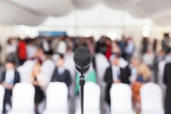 Business conference. Corporate presentation. Microphone. Microphone in focus against blurred audience. Participants at the business or professional conference royalty free stock photos