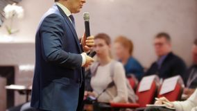 A business conference in the hall. A man talking on the stage and giving a lecture to the audience stock images