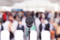 Business conference. Microphone. Corporate presentation. Participants at the business or professional conference. Microphone in focus against blurred audience royalty free stock photography