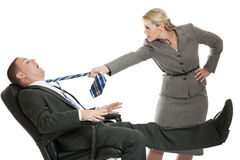 Business conflict. An angry business women pulling the tie of a business men isolated on white Stock Photo