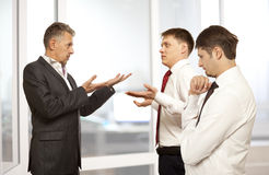 Business conflict concept. Three businessman are trying to come to an agreement Stock Photos