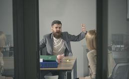 Business conflict and confrontation. Angry boss shout at accountant in office. Bearded man and woman discuss company. Business conflict and confrontation. Angry royalty free stock photography