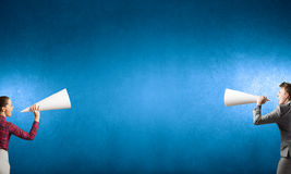 Business conflict. Two business people shouting in megaphones at each other Royalty Free Stock Photography