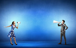 Business conflict. Two business people shouting in megaphones at each other Stock Photos