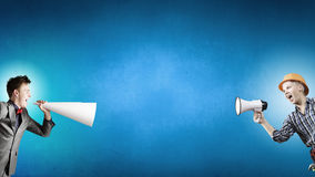 Business conflict. Two business people shouting in megaphones at each other Royalty Free Stock Photos