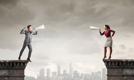 Business conflict. Two business people shouting in megaphones at each other Stock Image