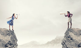Business conflict. Two women shouting in megaphones at each other Royalty Free Stock Photo
