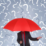 Business confusion. Businessman holding red umbrella with question mark rain concept for confusion, decisions or business recruitment Royalty Free Stock Photos