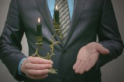 Business conspiracy. In search of investment. Business man holds a burning candle in a candlestick and illuminates the path to success. Leadership concept Stock Photos