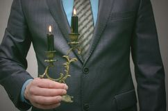 Business conspiracy. Shadow business. In search of investment. Business man holds a burning candle in a candlestick and illuminates the path to success Royalty Free Stock Photo
