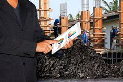 Business Construction Site, Businessman using tablet and Blurred background Construction workers. The Business Construction Site, Businessman using tablet and royalty free stock photo