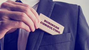 Business consulting. Businessman removing a wooden card reading Business consulting from the pocket of his suit jacket, vintage effect toned image Stock Images