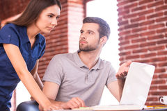 Business consulting. Handsome young men sitting at his working place and pointing computer while confident women standing close to him Stock Photo