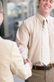 Business contact. Business one man and one woman standing smiling and shaking hands Stock Photos