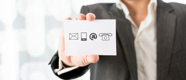 Business contact and information center. Closeup of businessman showing a white card with contact icons. Conceptual of business information center and support stock photo