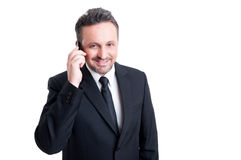 Business contact person using phone. Dressed with elegant suit and black tie Royalty Free Stock Photography