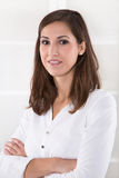 Business: content pretty brunette with folded arms in a white sh. Irt - medical assistant stock photo
