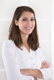 Business: content pretty brunette woman with folded arms in a white blouse. Smiling face stock photo