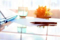 Business contract with pen is ready to sign. A glass of water. Business contract with pen is ready to sign stock photo