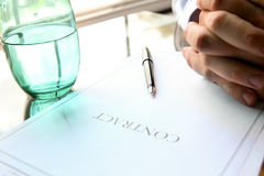 Business contract with pen is ready to sign. A glass of water. Business contract with pen is ready to sign stock photography
