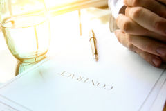 Business contract with pen is ready to sign. A glass of water. Business contract with pen is ready to sign royalty free stock image
