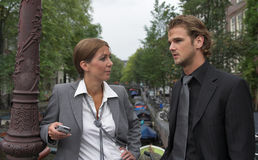 Business conversation. Businesswoman and businessman having a conversation outdoors; at an Amsterdam channel stock photography