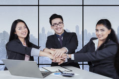Business cooperation with workers joining hands Stock Photography