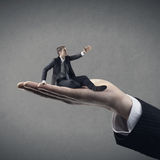 Business counseling. Huge hand helping young business on gray background royalty free stock photos