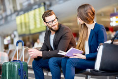 Business couple at the airport. Elegant business couple sitting with phone and book at the waiting hall in the airport. Business travel concept royalty free stock photo