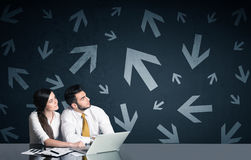 Business couple with arrows in background Royalty Free Stock Photos
