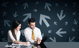 Business couple with arrows in background Royalty Free Stock Images