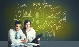 Business couple with business diagrams Royalty Free Stock Photos