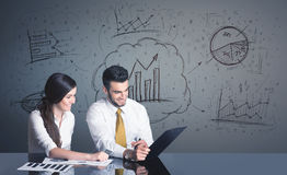Business couple with business diagrams Stock Image