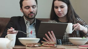 Business couple at cafe use tablet. While eating stock video